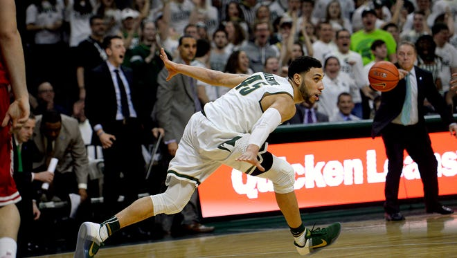 Spartans guard Denzel Valentine celebrates his dunk as Izzo yells at him to get back on defense during MSU's 69-57 victory over Wisconsin Thursday. Valentine finished with 24 points, 10 assists and seven rebounds.