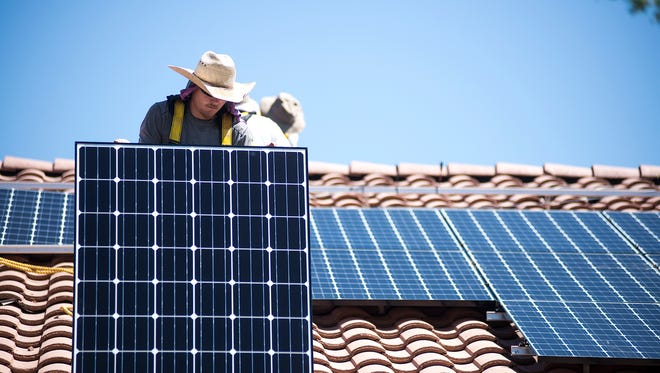James Hewitt prepares to hand Joe Segundo and Benjamin Jennings a solar panel during an installation in Buckeye, Ariz., on Tuesday, July 7, 2015.