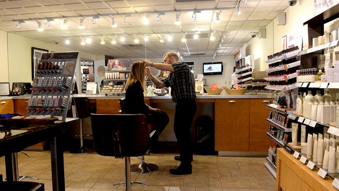 A colorist at Douglas J Salon and Day Spa in Okemos applies makeup to a model last fall. Staff from the salon's East Lansing location will be moving to the Okemos facility on May 2.