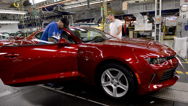 Workers look over a 2016 Camaro as it rolls down the assembly line  on Monday, Oct. 26, 2015 at GM's Lansing Grand River plant. The plant fully transitioned into a third shift this week.