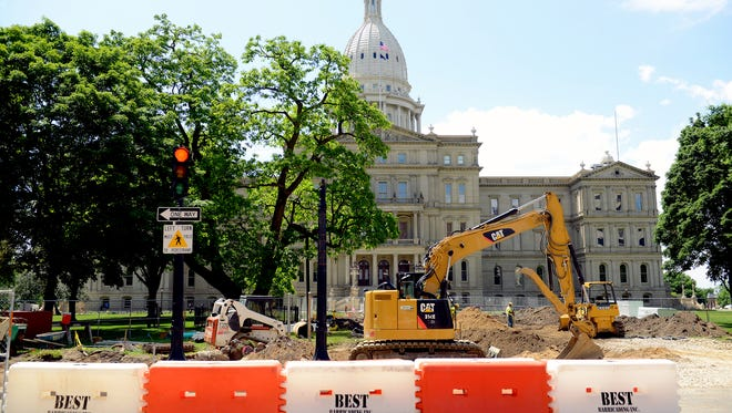 Workers restore and replace the walkway on the east side of the Capitol Building Monday, July 6, 2016, in Lansing. The walkway, according to John Truscott, vice-chairman of the Capitol Commission, is part of a long-term project to restore the building and grounds to its historic significance. Work is scheduled to be completed July 8.