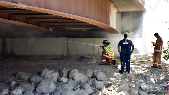 Reno Firefighters put out a debris fire under the Sutro Street bridge over the Truckee River at noon, June 10, 2016.