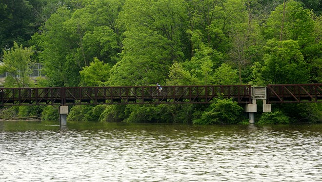 A man rides his bike on a bridge over the Grand River at Lansing's Moore's River Park last summer.