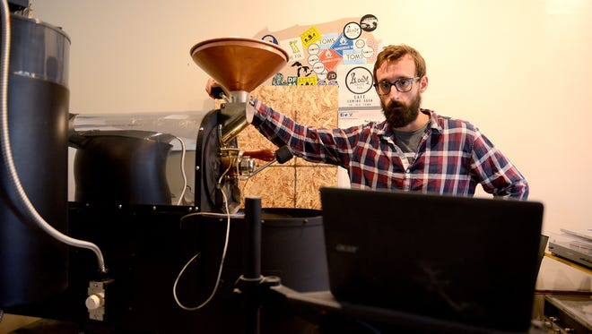 Jared Field, owner of Bloom Roasters, watches the progress of the roasting process on a laptop to make sure the temperature doesn't get too high, or low, Monday, June 20, 2016 in Old Town Lansing. He plans of opening the pour-over cafe on July 5, with limited hours on July 1 during Arts Night Out. He said he was drawn to Old Town because it's an artsy community, and he considers roasting his art form.