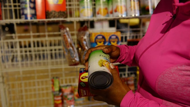 A woman picks up canned goods at the Pagans In Need food pantry on Washington Avenue in Lansing on Saturday, July 16, 2016. The pantry also offers clothes and fresh vegetables from a community garden.