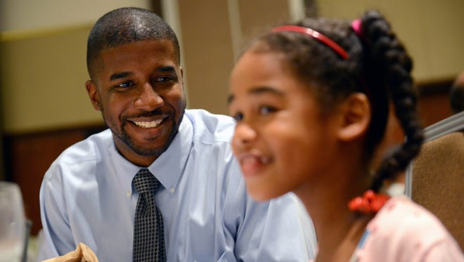 Former Waverly High School and MSU basketball player Marcus Taylor smiles at his daughter Zoe, 6, as they joke around during the the Lansing Sports Hall of Fame banquet Thursday, July 28, 2016 at the Lansing Center. Taylor's 2000 state championship basketball team was being inducted into the hall.