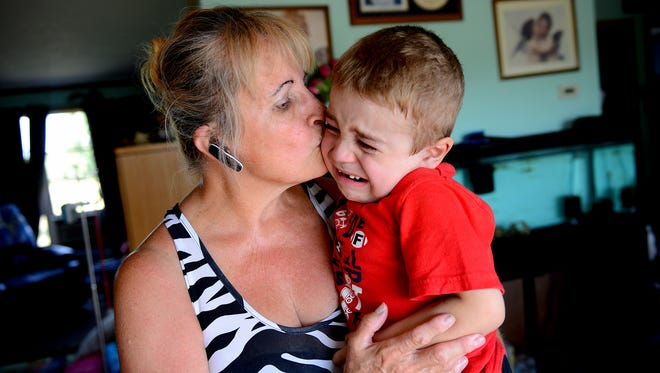 Leona Simon, 66, of Grand Ledge, picks up her grandson Carl Cole, 5, after he became upset that he wasn't allowed to play outside at her home in Grand Ledge. Simon is Carl's full-time caregiver and she didn't want him outside in the 90-plus degree heat. Carl has Duchenne Muscular Dystrophy, a progressive genetic condition that causes muscle weakness. He also has a spinal curvature and only one lung and kidney, among other medical conditions. Simon drives Carl to school in Ionia and to doctor and therapy appointments in Ann Arbor, Grand Rapids, Lansing and Brighton. Her van, with nearly 300,000 miles, broke down. She cannot afford a new vehicle so she's turning to an online fundraiser for help.