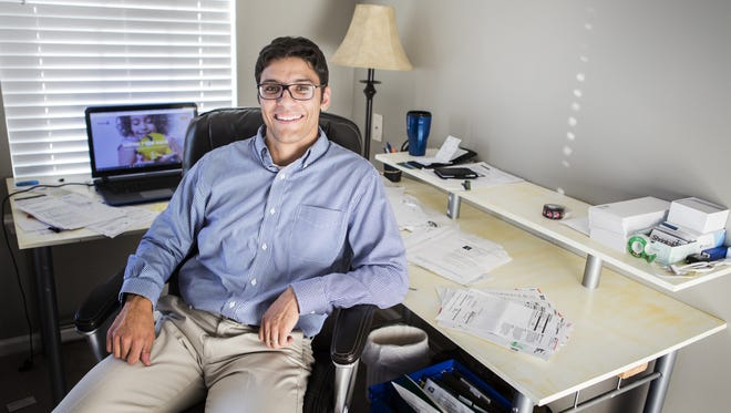 Jordan Wolff sits surrounded by bills in his Port Penn-area home office. The 29-year-old is the founder of Shrinkabill, a startup that negotiates with service providers to get lower rates for its clients.