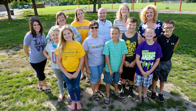 """Members of the """"Friends of Wacousta Playground Project"""" stand in the footprint of the former playground at the Wacousta Elementary School Wednesday, Aug. 24, 2016 in Wacousta. The group has nearly raised $200,000 to build a new playground for the school. According to Cory Dykhuizen, a general coordinator of the group, many of the members are alumni of the school and have a great sense of community. They were there for the original one to be built and to have it taken down was emotional for them. He said students spent all last year without a playground and that he sees this as a way to give back and provide for the community."""