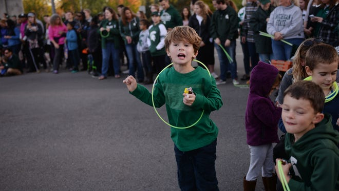 Jack Short, 5, jumps up and down for candy during MSU's homecoming parade on Friday, Oct. 14, 2016 in East Lansing.