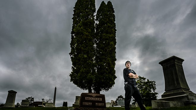 Brad Mikulka,  a paranormal investigator, stands in Mount Hope Cemetery Friday October 21, 2016 in Lansing.