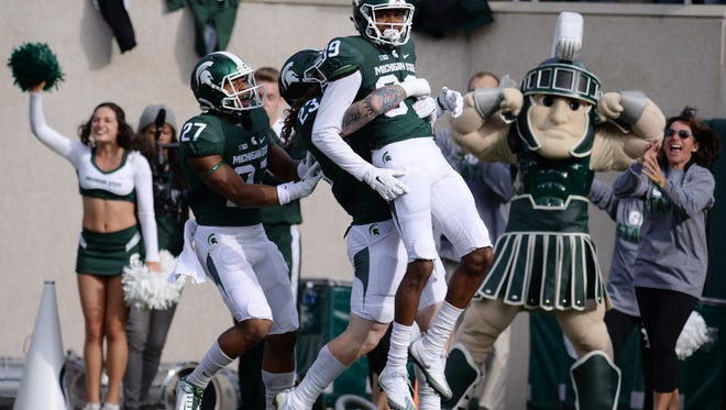 Junior linebacker Chris Frey lifts up freshman cornerback Justin Layne after Layne intercepted the ball and ran in for a touchdown during the game against Northwestern on Saturday, Oct. 15, 2016 at Spartan Stadium in East Lansing.