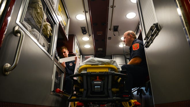 Lansing firefighters/paramedics Eric Wohlfert, left, and Steve Davich check on the systems in the ambulance while going through routine maintenance at Fire Station 1 on Friday, Nov. 11, 2016, in Lansing.  The Legislature is discussing reforms to municipal retirement systems, like the one Lansing firefighters have.