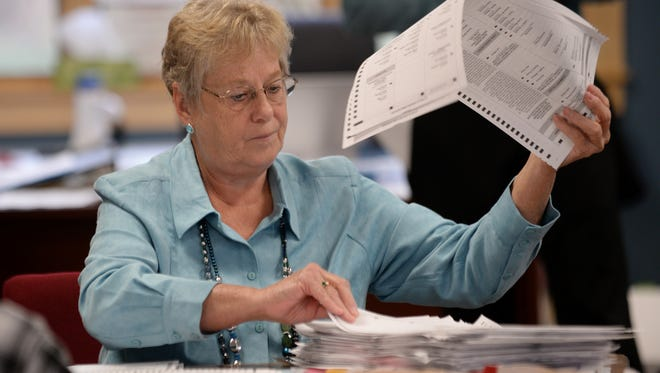 A recount worker with Eaton County counts out ballots during the recount on Wednesday, Dec. 7, 2016 at Carmel Township Hall in Charlotte.