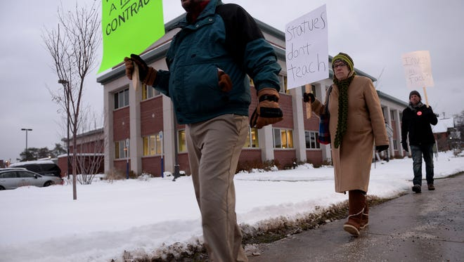 People protest faculty contract issues Monday in front of the Lansing Community College Administration Building. Staff have worked without a contract since August.
