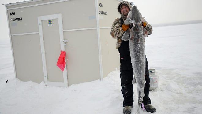 Scott Ash poses with his catch during the lake sturgeon fishing season on Black Lake on Saturday, Feb. 4, 2017, in Cheboygan County.