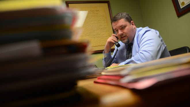 Attorney Patrick Crowley, who often represents indigent defendants in Ingham County, makes a phone call on Friday, Feb. 24, 2017 at the  law firm Crowley, Cornish, Rockafellow, & Sartz in Lansing. County officials are concerned the state may not come through on promised investments in indigent defense systems.