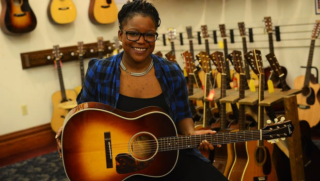 HR Director Lillian Werbin poses for a portrait with a Farida Old Town series guitar on Wednesday, March 1, 2017 at Elderly Instruments in Lansing.