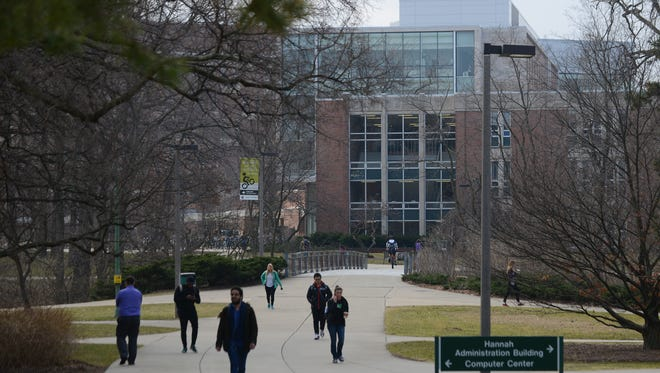 People walk on Wednesday, Feb. 22, 2017 at Michigan State's campus in East Lansing. The building pictured is Wells Hall.