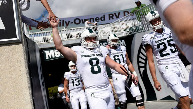 From left, Michigan State's Mickey Macius, Brett Scanlon, Cole Chewins and Jake Hartbarger take the field wearing their all-white uniforms before the Spartans' game against Western Michigan on Saturday, Sept. 9, 2017, at Spartan Stadium in East Lansing. The Spartans haven't worn all-white uniforms since 1954.