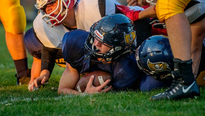 Pewamo-Westphalia quarterback Jimmy Lehman, center, looks up after crossing the goal line for a touchdown during the first quarter of the Pirates' game against Laingsburg's on Friday, Sept. 29, 2017, in Westphalia.