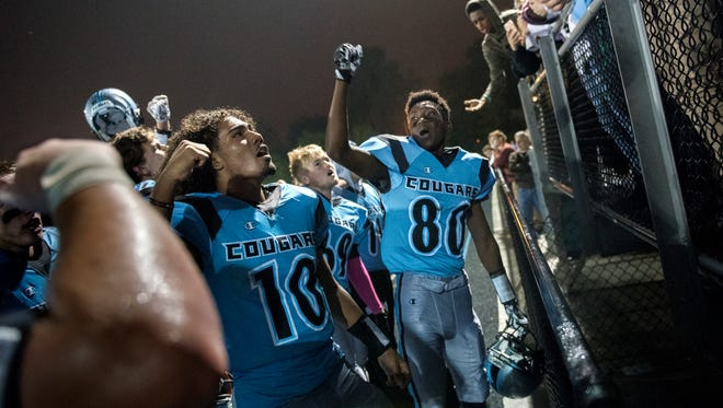 Lansing Catholic's Michael Lynn III, left, Roje Williams, right, and the rest of the Cougars' celebrate their Oct. 6 victory over Ionia on Friday at Cougar Stadium in Lansing.