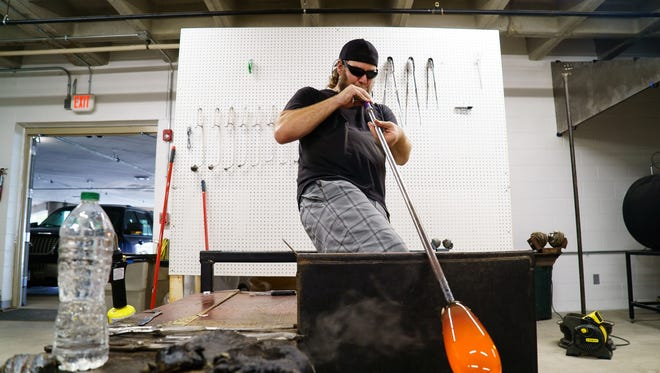Glass blower Jesse Ahrendsen works on making a pumpkin in the JJGaffers Glassblowing Studio at the renovated Mainframe studios on Oct. 18, 2017, in Des Moines.