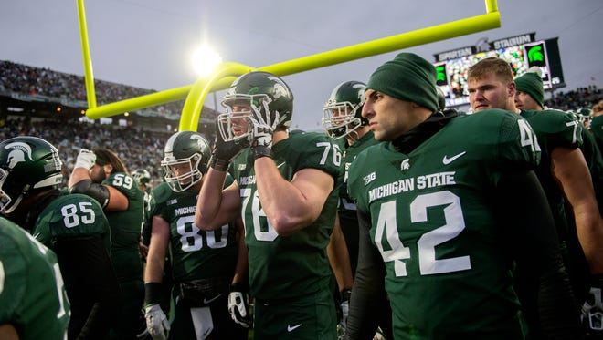 The Michigan State Spartans head to the locker room after a game delay for extreme weather during the second quarter on Saturday, November 4, 2017, at Spartan Stadium in East Lansing.