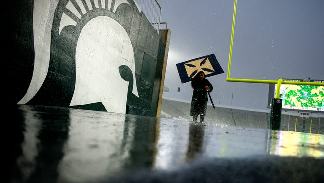 A member of the MSU band staff carries a prop that was to be used during the halftime show in the Spartans' game against Penn State during a rain delay on Saturday, November 4, 2017, at Spartan Stadium in East Lansing. The band halftime show was canceled.