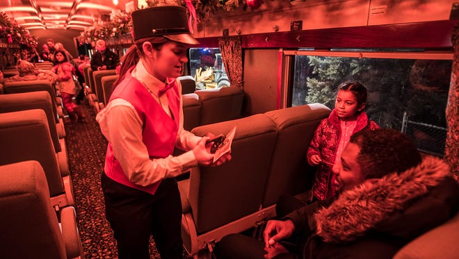 Conductor Angela Price punches a ticket for Ava Berroa, 6, of Rutherford at the Polar Express event at the Whippany Train Museum on Thursday.