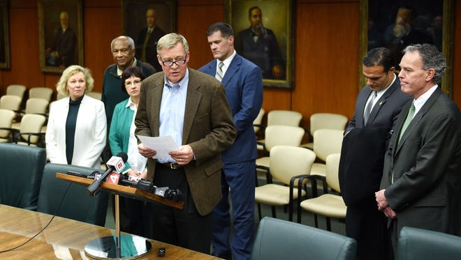Michigan State University Board of Trustees Chairman Brian Breslin, center, reads a statement regarding MSU President Lou Anna K. Simon during a press conference on Friday, Jan. 19, 2018, in the Hannah Administration Building on the MSU campus in East Lansing. Breslin and fellow board member Mitch Lyons aren't running for reelection this year. The open race has drawn lots of interest from candidates and voters.