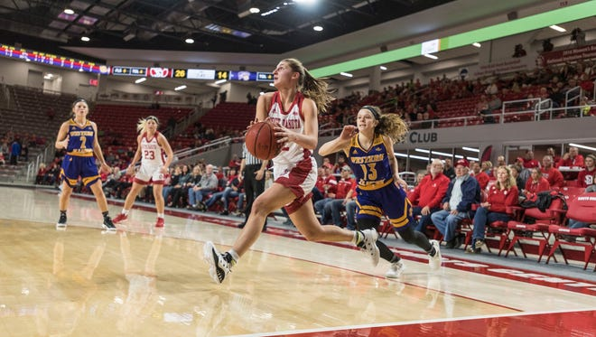 Jayee Bradley drives to the basket past Olivia Kaufman on Thursday night vs. Western Illinois at the Sanford Coyote Sports Center.