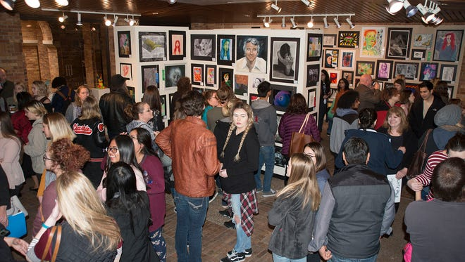 Dozens of people browse through the artwork at the 27th Annual High School Art Competition in the Foyer Gallery at Midwestern State University.