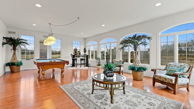 The sun-drenched conservatory features arched divided-light windows, hardwood floors and recessed lights.