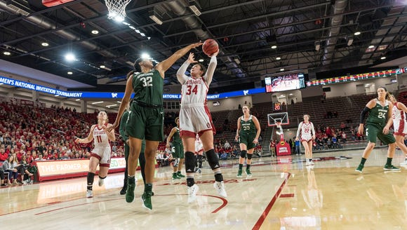 South Dakota's Kate Liveringhouse shoots over Michigan State's Taya Reimer. The Coyotes will face Texas Christian on Sunday night at the SCSC.