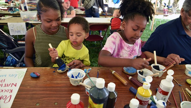 The Ray Children Ahniah, 13, holds Isaih,2, and Gracey, 8, paint rocks during the 19th annual EarthFest at Knoxville Botanical Garden and Arboretum on Saturday, April 28, 2018.((J. Miles Cary/Special to the News Sentinel)