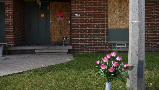 A vase of plastic flowers adorns the front yard at 2436 REO Road on June 12, 2018 in the LaRoy Froh complex in south Lansing. A June 7 fire there killed Tarshrikia Beasley, 43, and her 5-year-old son Elijah Brown.