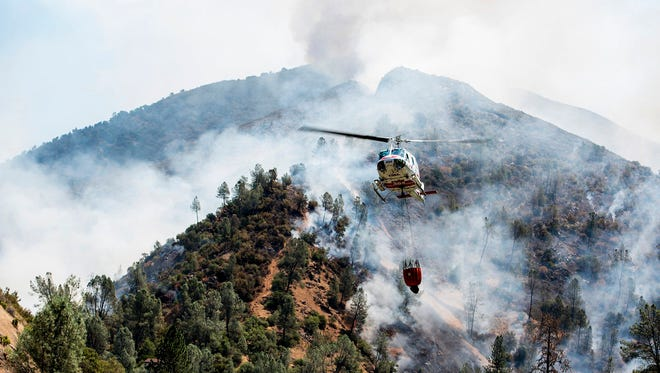 A helicopter gathers water from the Merced River to fight the Ferguson Fire along steep terrain behind the Redbud Lodge near El Portal along Highway 140 in Mariposa County, Calif., on Saturday, July 14, 2018.