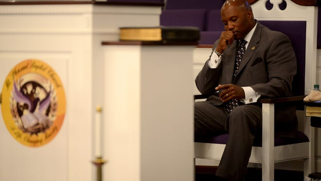 Jackson Police Department SWAT Officer and Minister Derick Tisdale meditates before preaching a sermon at Mt. Pleasant Baptist Church in Pinson, Sunday, Nov. 16, 2014.