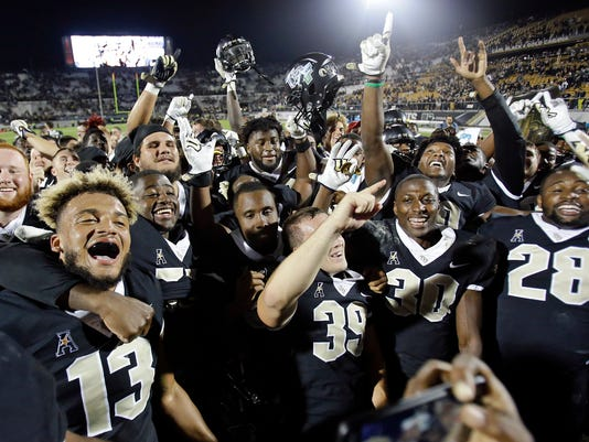 Central Florida players celebrate after defeating South Florida 49-42 in an NCAA college football game, Friday, Nov. 24, 2017, in Orlando, Fla. (AP Photo/John Raoux)