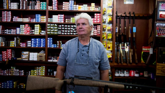Randy Maney of Allen's Gun Shop stands in their storefront in the aftermath of the shooting in Las Vegas, which has heightened the debate over gun rights once again.