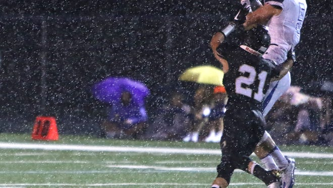 Under a heavy rain, Franklin's Aaron Simmons (21) brings down Oak Creek's Troy Chmielewski (5) during a recent Sabers' victory. Franklin beat Kenosha Indian Trail on Sept. 30.