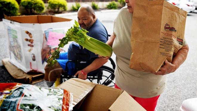 Julia Melendez, of York City, picks up fresh produce with her husband, Raymond Mendoza, during a pop-up market at the York County Food Bank on Wednesday, May 30, 2018. Debbie Krout, director of operations and programs for the food bank, said the bank had an extra amount of perishable items after the Memorial Day holiday, during which the bank skipped its normally scheduled food offering. In addition to its Food for Families each Friday, the bank now offers fresh produce Mondays during its pop-up market from 10:30 a.m. to 1:30 p.m. Bill Kalina photo