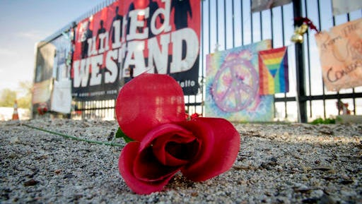 An artificial flower lays in front of memorial items displayed at the Inland Regional Center, the site of last year's terror attack, in San Bernardino, Calif., Thursday Dec. 1, 2016. Friday will mark the one year anniversary of the attack.