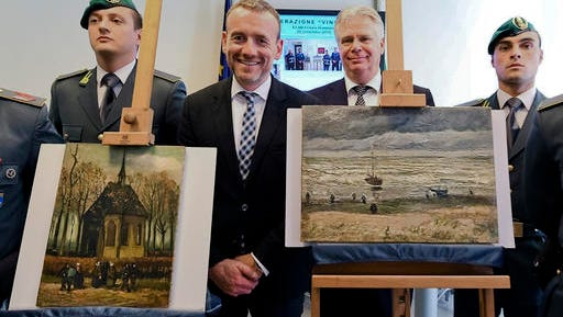 FILE- In this  Friday, Sept. 30, 2016 file photo, Director of Amsterdam's Van Gogh Museum Axel Rueger, center, stands next to the paintings 'Congregation Leaving The Reformed Church of Nuenen', left, and 1882 'Seascape at Scheveningen' by Vincent Van Gogh, during a press conference in Naples, Italy.  Two paintings by Vincent van Gogh that were stolen in 2002 from the Amsterdam museum that is named for the Dutch master and recovered last year by Italian police are set to be returned.