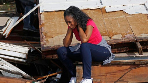Shanise McMorris grieves on the slab of her Hattiesburg, Miss., home after an early tornado hit the city, Saturday, Jan. 21, 2017.  The tornado was part of a wall of stormy weather traveling across the region, bringing with it rain and unstable conditions.