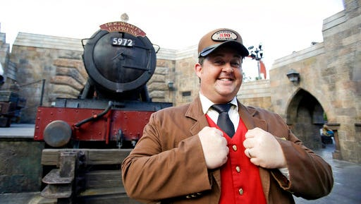 FILE - In this Thursday, Oct. 22, 2015 file photo, a station agent greets guests in front of the Hogwarts Express train at the Wizarding World of Harry Potter at Universal Studios in Orlando, Fla. Comcast has spent billions of dollars refurbishing and expanding its park empire, growing into Asia and adding rides and attractions to its California and Florida destinations.