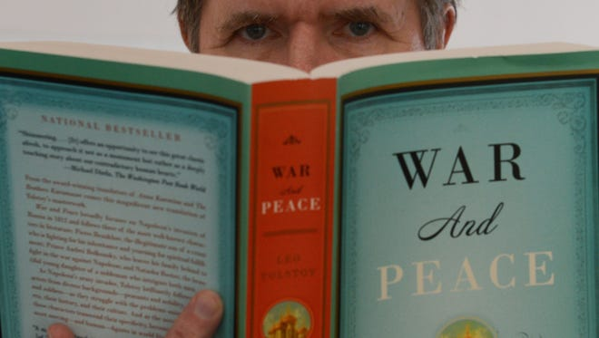 "A man holds a copy of Richard PevearandLarissa Volokhonsky's translation of Leo Tolstoy's ""War and Peace."""