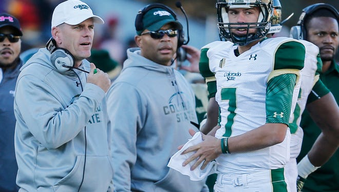 Mike Bobo, CSU's first-year coach, left, talks to quarterback Nick Stevens on the sideline during the Rams' 26-7 win Saturday at Wyoming.