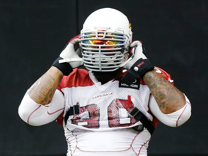 Cardinals DT Darnell Dockett puts his practice helemt on during training camp at University of Phoenix Stadium July 29, 2014. The league won't let him play with this during the season.